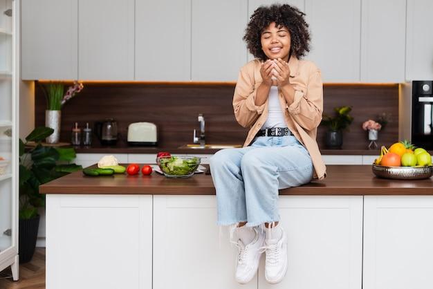 Vista frontal mulher segurando uma xícara de café na cozinha Foto gratuita