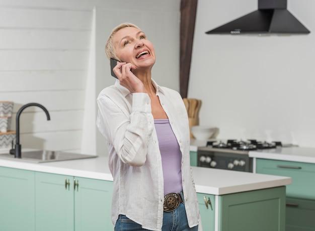 Vista frontal mulher sênior falando no telefone Foto gratuita