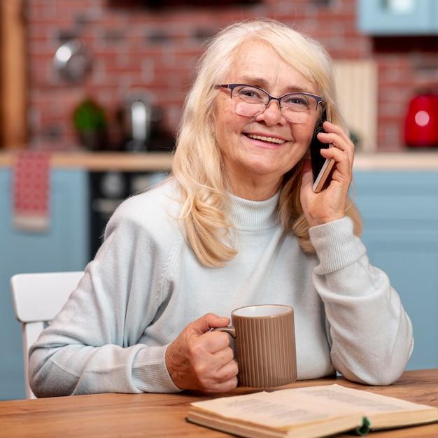 Vista frontal mulher sênior falando por telefone Foto gratuita