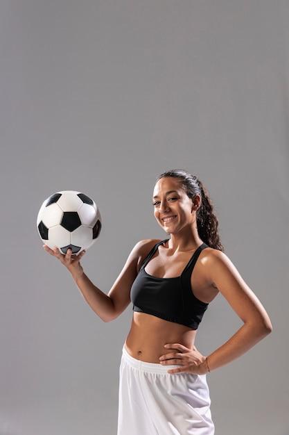 Vista frontal mulher sorridente com bola de futebol Foto gratuita