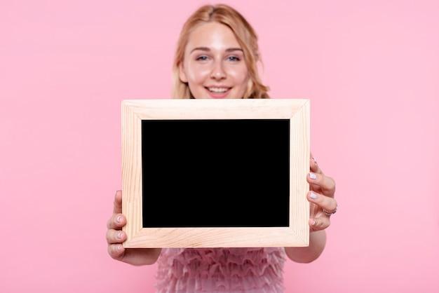 Vista frontal mulher sorridente mostrando quadros Foto gratuita