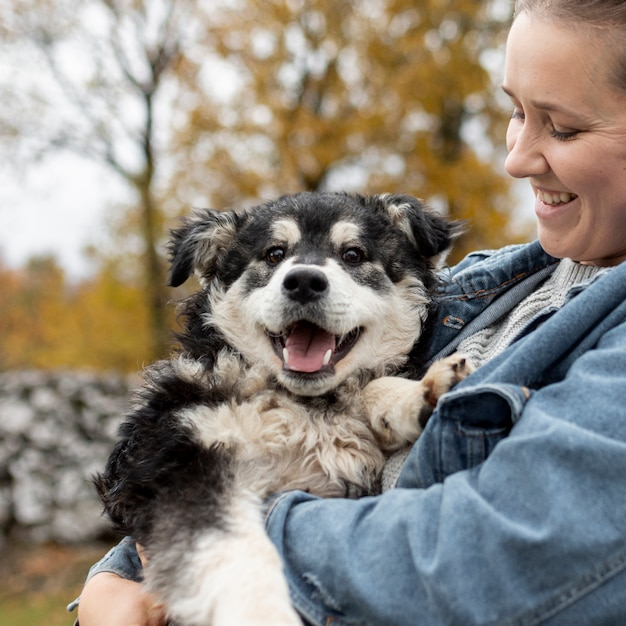 Vista frontal mulher sorridente segurando cachorro fofo Foto gratuita