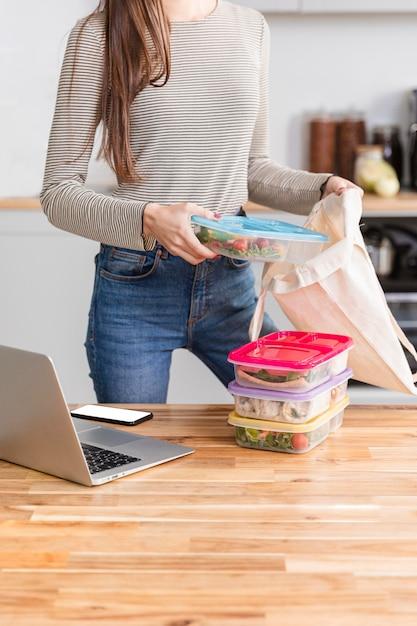 Vista frontal mulher trabalhando em casa e comida Foto gratuita