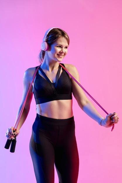 Vista frontal mulher treinando com pular corda Foto gratuita