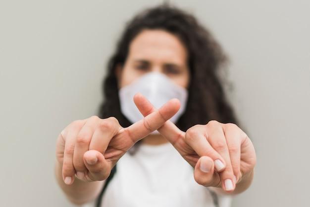Vista frontal mulher vestindo máscara médica e formando um x com os dedos Foto gratuita