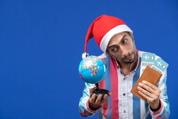 Vista frontal normal masculino com ingressos e globo na parede azul emoção feriado ano novo Foto gratuita