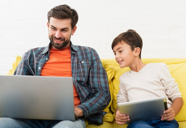 Vista frontal pai e filho olhando no laptop Foto gratuita