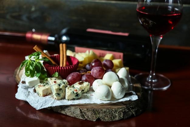 Vista frontal queijo prato mistura de queijos com uvas e mel com um copo de vinho tinto Foto gratuita