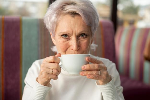 Vista frontal sênior feminino bebendo café Foto gratuita