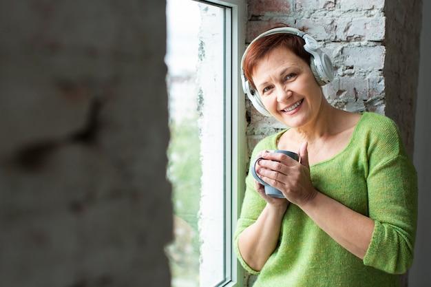 Vista frontal, smiley, ancião, escutar música Foto gratuita