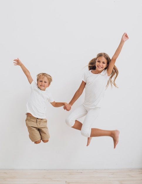 Vista frontal sorridente irmãos pulando Foto gratuita
