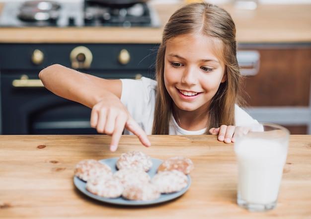 Vista frontal sorridente menina tomando um delicioso biscoito Foto gratuita