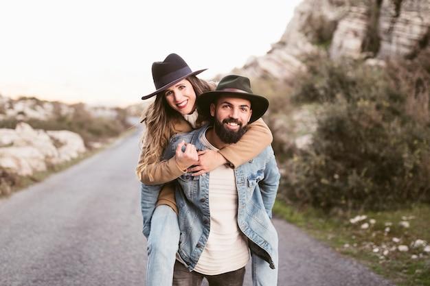 Vista frontal sorrindo homem e mulher em uma estrada de montanha Foto gratuita