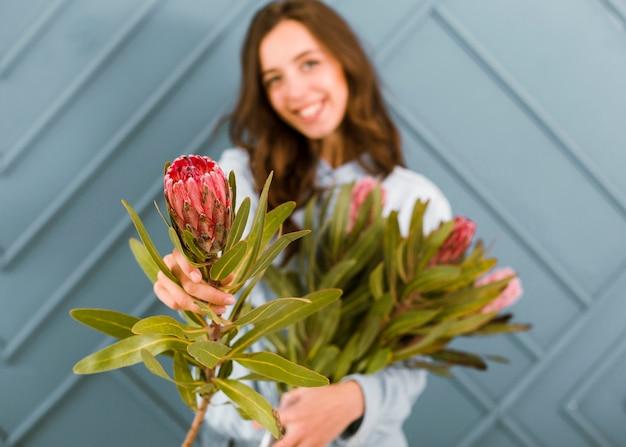 Vista frontal turva mulher posando com flores Foto gratuita