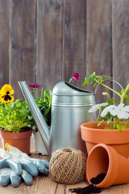 Vista frontal vasos de flores e ferramentas de jardinagem Foto gratuita