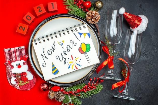 Vista horizontal do caderno com escrita e desenhos de ano novo pratos de jantar acessórios de decoração ramos de abeto xsmas taças de vidro na mesa escura Foto gratuita