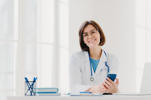 Vista horizontal do médico profissional sorridente trabalha na clínica, posa no escritório do hospital moderno com aparelhos eletrônicos Foto Premium