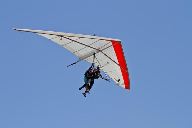 Vista incrível de humanos voando em uma asa delta isolada em um fundo de céu azul Foto gratuita