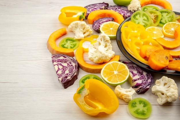 Vista inferior corte legumes e frutas abóbora pimentões caqui repolho vermelho tomate verde na placa preta na mesa de madeira Foto gratuita