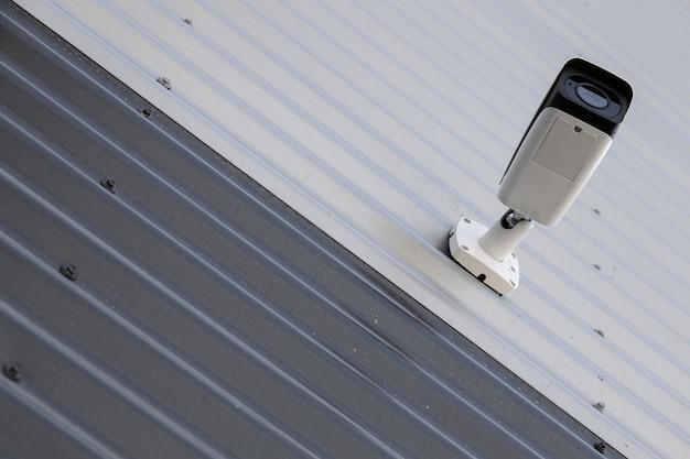 Vista inferior da câmera de monitoramento de vídeo preto e branco de alta tecnologia na parede ondulada em preto e branco Foto Premium