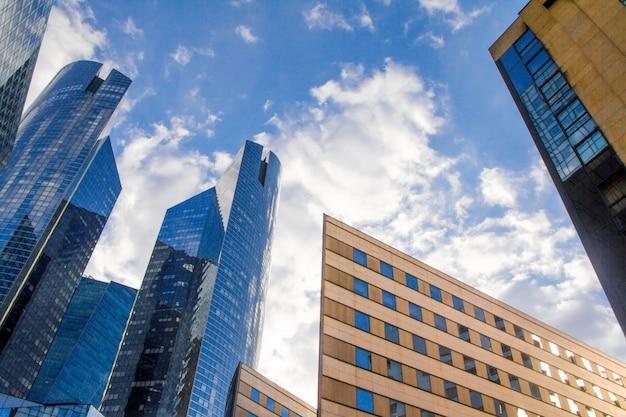 Vista inferior dos arranha-céus de vidro da área empresarial de paris la defense contra um céu azul nublado Foto Premium
