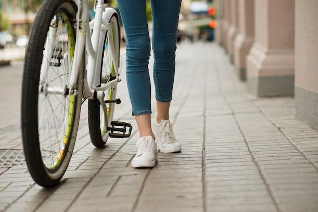 Vista inferior mulher andando ao lado de bicicleta Foto gratuita