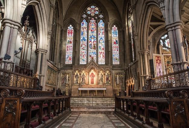 Vista interna de uma igreja com ícones religiosos nas paredes e janelas Foto gratuita
