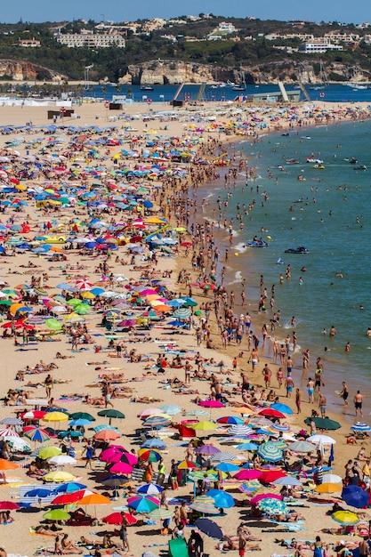 Vista larga de uma praia aglomerada em portimao, portugal. Foto Premium