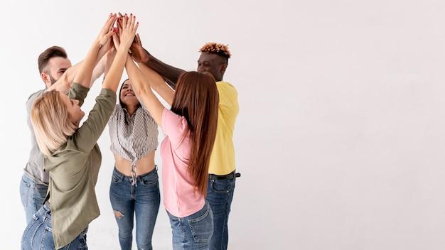 Vista lateral amigos com as mãos levantadas Foto gratuita