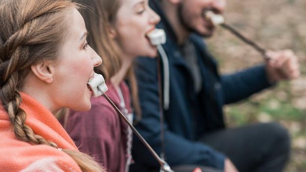 Vista lateral amigos comendo marshmallow Foto gratuita