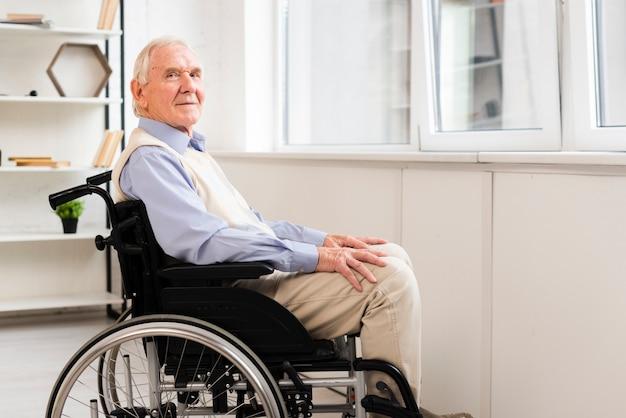 Vista lateral, ancião, sentando, ligado, cadeira rodas Foto gratuita