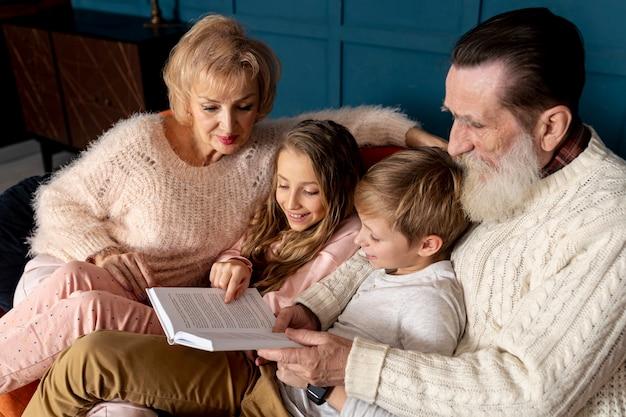 Vista lateral avós lendo um livro com seus netos Foto gratuita