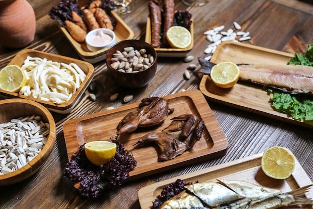 Vista lateral cerveja lanches peixe defumado codorniz defumado queijo trança sementes pistache com limão em cima da mesa Foto gratuita