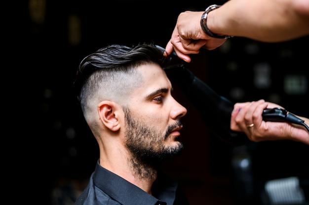 Vista lateral costumer no salão de cabeleireiro Foto gratuita