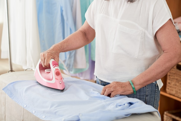 Vista lateral da camisa de passar roupa de seção intermediária feminina em casa Foto gratuita