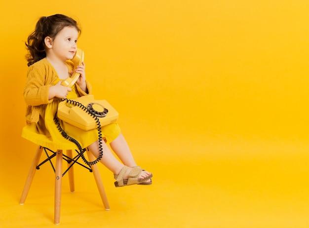 Vista lateral da criança adorável posando com telefone Foto gratuita