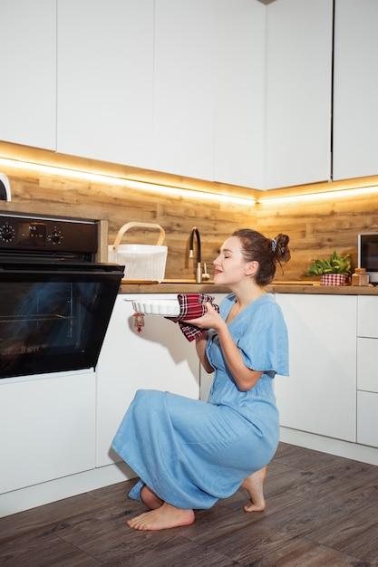 Vista lateral da encantadora mulher loira encaracolada caucasiana no avental tirando do forno assado alimentos. interior da cozinha doméstica. mulher tomando assadeira. conceito de culinária caseira. Foto Premium