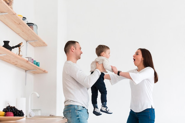 Vista lateral da família feliz com criança na cozinha Foto gratuita