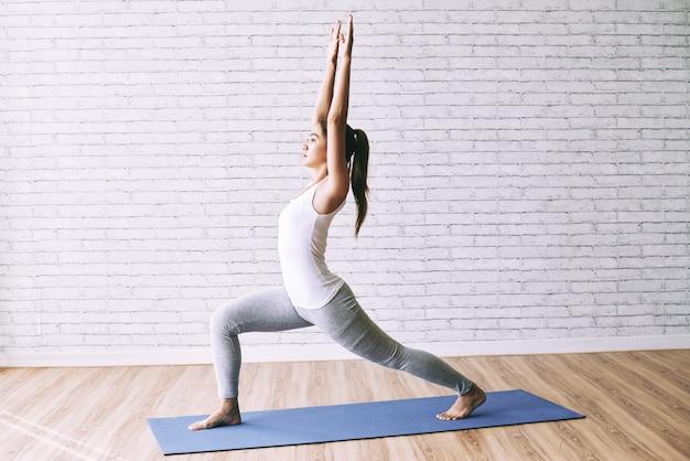 Vista lateral da garota apta praticando ioga, fazendo uma pose de guerreiro no tatame Foto gratuita