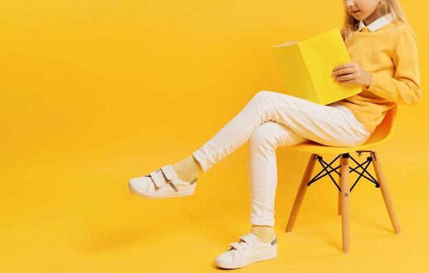 Vista lateral da garota posando ao ler o livro Foto gratuita