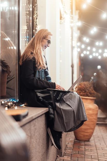 Vista lateral da jovem mulher usando laptop na rua com a cidade à noite Foto gratuita