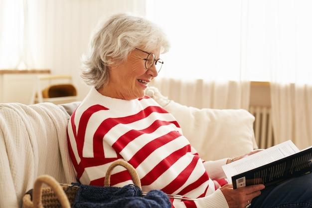 Vista lateral da linda avó feliz de óculos, apreciando a leitura dentro de casa, sentado no sofá com uma história de detetive interessante, sorrindo com alegria. mulher idosa elegante relaxando no sofá segurando um livro Foto gratuita
