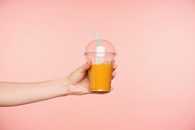Vista lateral da mão da jovem sendo levantada, segurando o suco fresco com canudo nele, isolado sobre o fundo rosa. conceito de fotografia de alimentos e bebidas Foto gratuita
