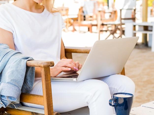 Vista lateral da mulher ao ar livre na cadeira trabalhando no laptop Foto gratuita