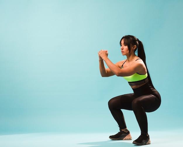 Vista lateral da mulher atlética em roupa de ginástica fazendo agachamentos com espaço de cópia Foto gratuita