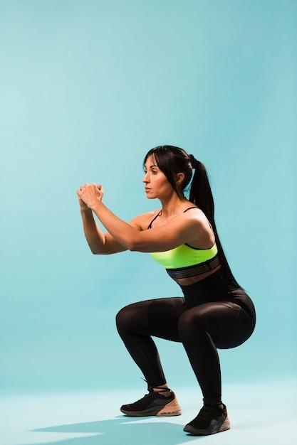 Vista lateral da mulher atlética em roupa de ginástica fazendo agachamentos Foto gratuita
