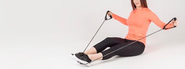 Vista lateral da mulher atlética, exercitar-se com banda de resistência Foto gratuita