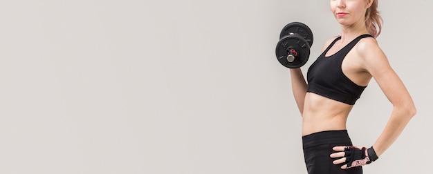 Vista lateral da mulher atlética, levantamento de peso com espaço de cópia Foto gratuita