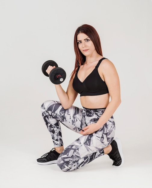 Vista lateral da mulher atlética, levantamento de peso Foto gratuita