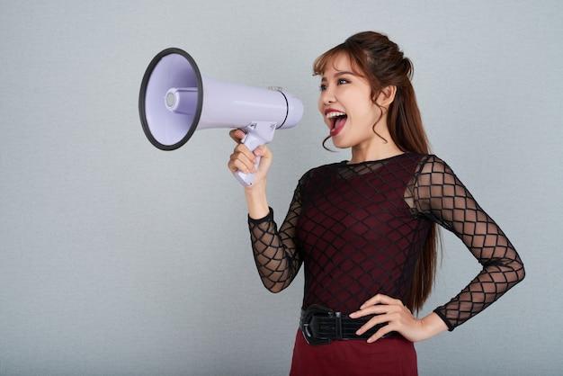 Vista lateral da mulher atraente, gritando no megafone com o braço na cintura Foto gratuita